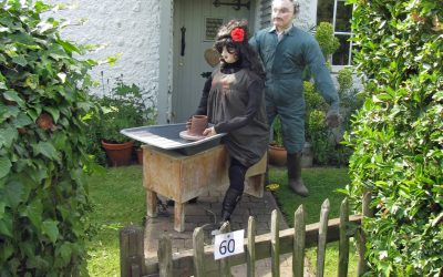 Maker in clay makes scarecrow